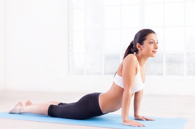 Женщина работает. вид сбоку привлекательной молодой индийской женщины, тренирующейся на коврике для йоги