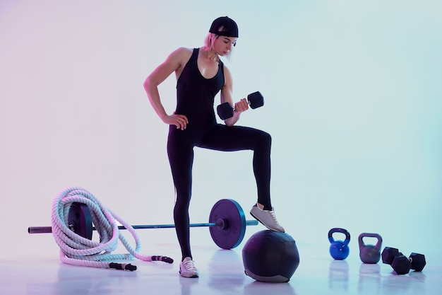 Woman working out with dumbbells woman surrounded by sports equiment
