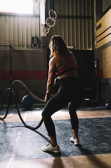 Woman working out with rope in gym