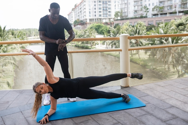 トレーナーと一緒に運動する女性