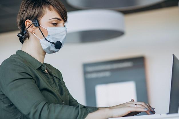Donna che lavora in studio di registrazione e indossa la maschera