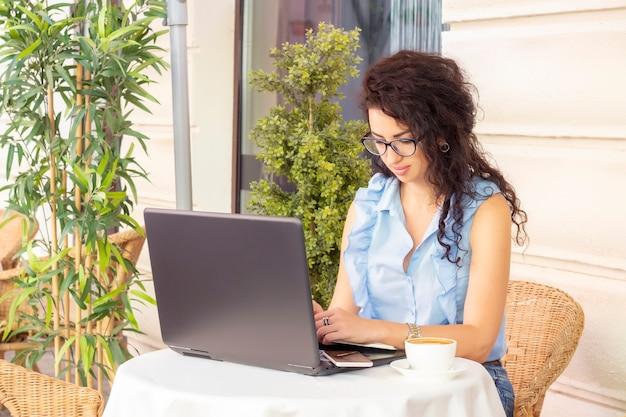 Woman working remotely with laptop in cafe. happy businesswoman using notebook in cafe. freelance