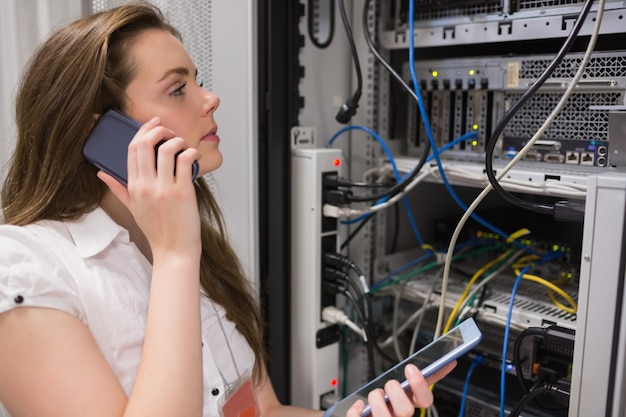 Woman working on servers with tablet pc on the phone