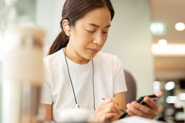 Woman working on smartphone with wireless earphones in cafe.