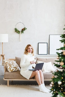 Woman working or studying on a computer, interior is decorated for christmas