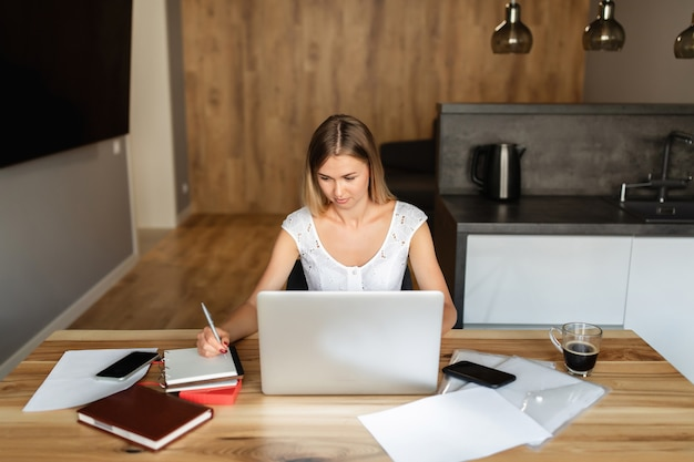 Woman working and studying on laptop at home office