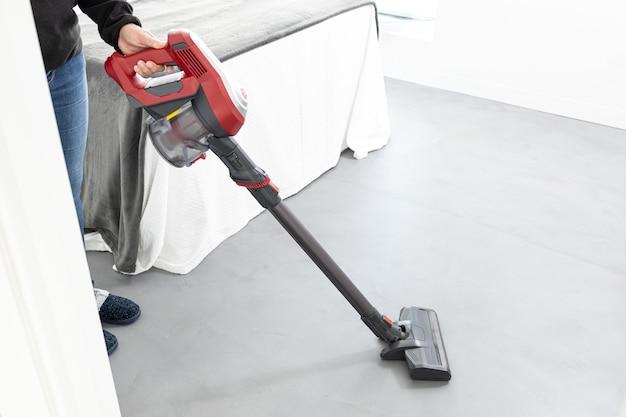 Женщина работает с беспроводным пылесосом в современной спальне дома