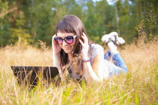 Женщина работает с ноутбуком посреди поля летом