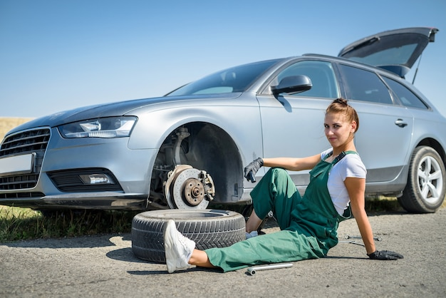 Woman working with broken wheel of her car, waiting for help