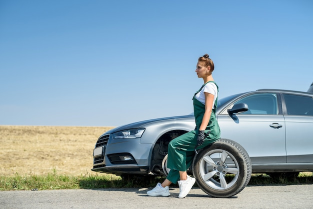 도움을 기다리는 그녀의 차의 깨진 바퀴로 작업하는 여자