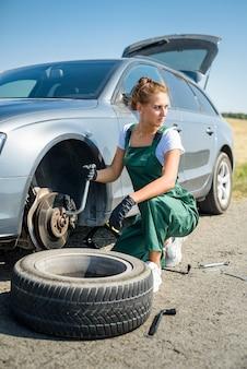 도움을 기다리는 그녀의 차의 깨진 바퀴로 작업하는 여자 프리미엄 사진