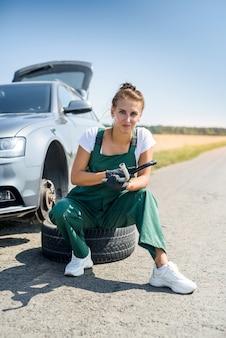 도움을 기다리는 그녀의 자동차의 깨진 된 바퀴를 사용하는 여자