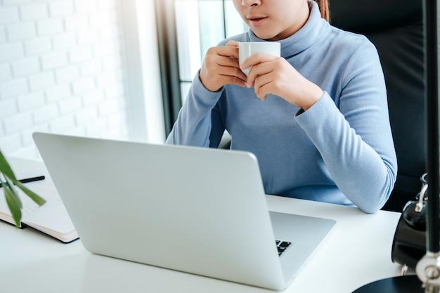 防護マスクを身に着けているコンピューターで働く女性