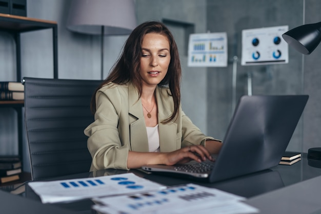 Woman working with documents and laptop sitting at her desk.