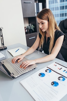 Woman working with documents sitting at desk in office.