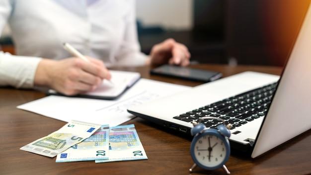 テーブルの上で財政を扱う女性。ノートパソコン、スマートフォン、お金、メモ帳、時計