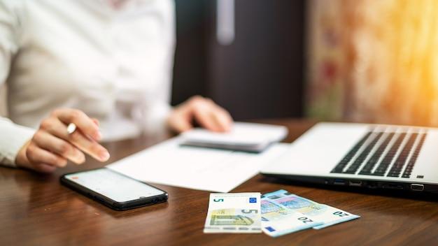 テーブルの上で財政を扱う女性。ノートパソコン、スマートフォン、お金、メモ帳