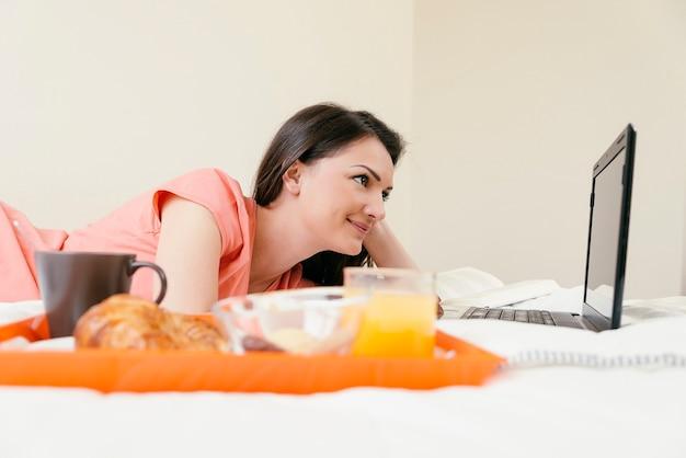 Женщина работает со своим портативным компьютером и завтракает. она в своей спальне.