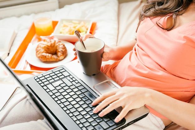 Женщина работает со своим портативным компьютером и завтракает