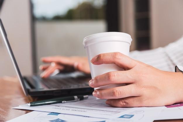 ノートパソコンで作業し、使い捨てカップからコーヒーを飲む女性
