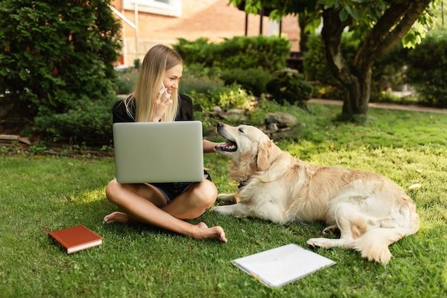 Женщина работает с ноутбуком и играет с собакой лабрадор в парке