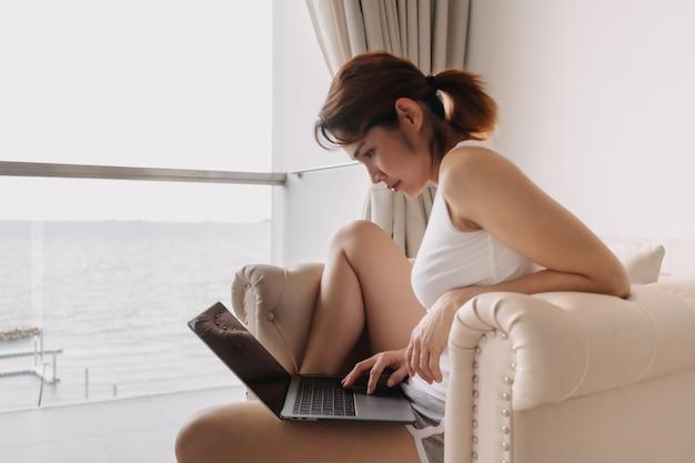 ノートパソコンで作業し、ホテルのソファでリラックスする女性