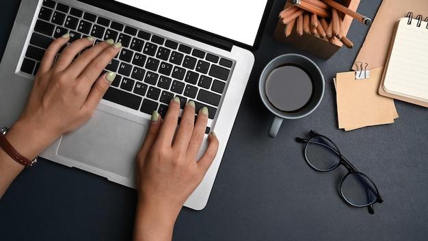 Женщина, работающая с портативным компьютером на черной коже.