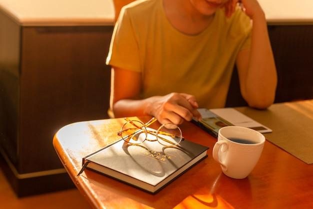 Женщина, работающая с мобильным телефоном с чашкой кофе на столе.