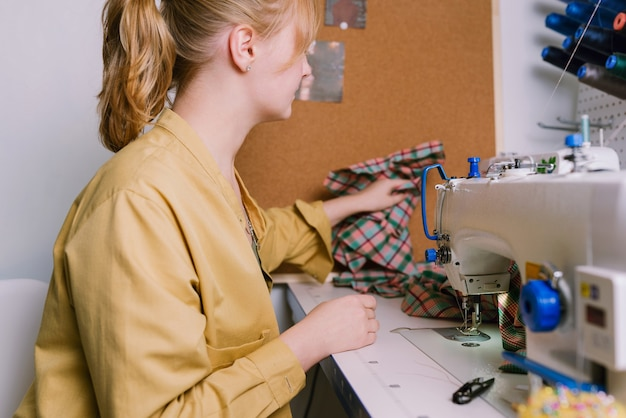 Woman working with sewing machine in her workshop
