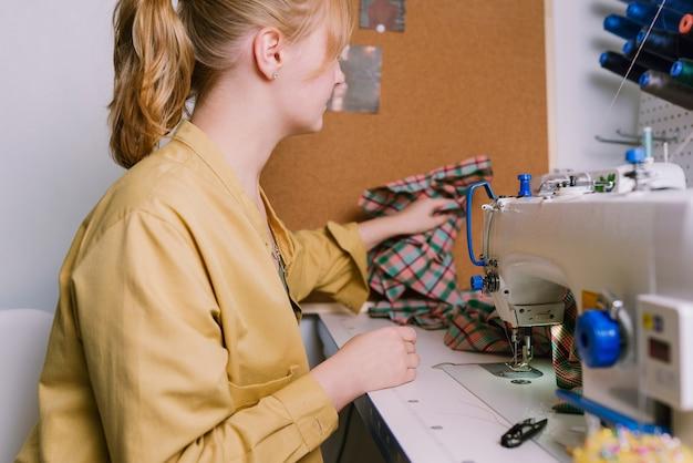 Женщина работает со швейной машиной в своей мастерской