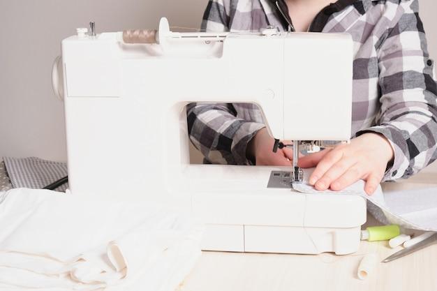 Женщина, работающая со швейной машиной, белая швейная машина на столе, процесс пошива швейных материалов