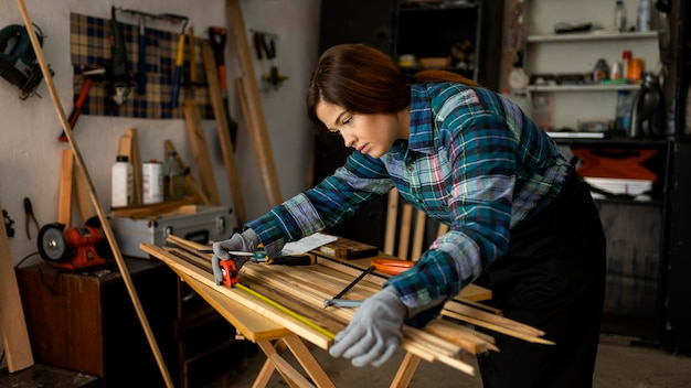 Woman working in workshop measuring