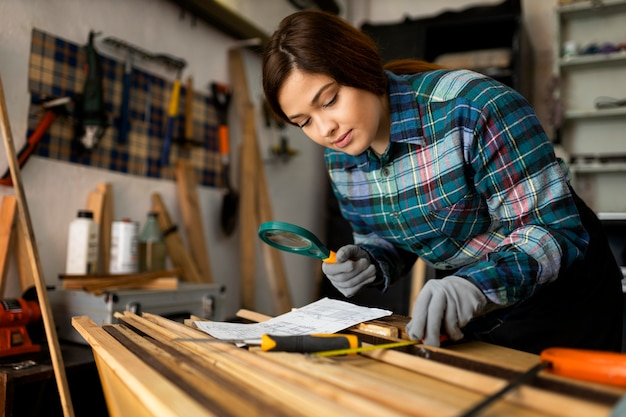 Woman working in workshop with magnifier glass