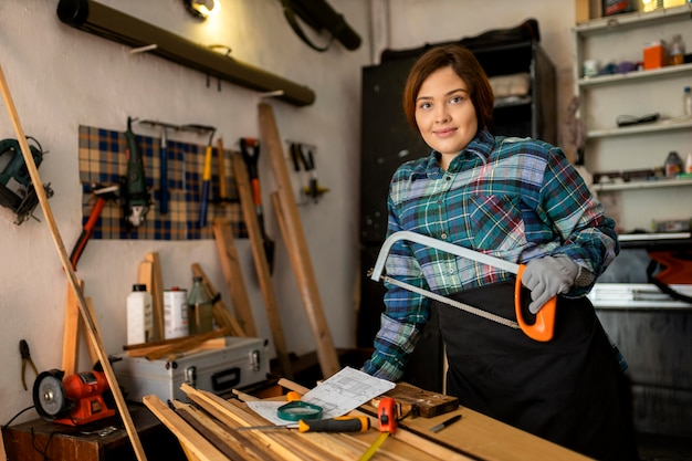 Woman working in workshop with saw