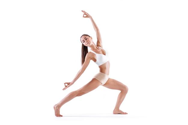 Упражнение йоги женщины работая, портрет в полный рост, изолированный на белизне. равновесие и медитация, гармония тела и разума.