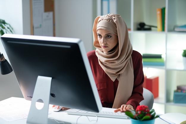働く女性。過負荷を感じてコンピューターに取り組んでいるヒジャーブを身に着けている若いイスラム教徒の女性