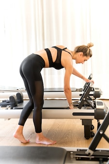 Woman in workout clothes adjusting reformer pilates bed