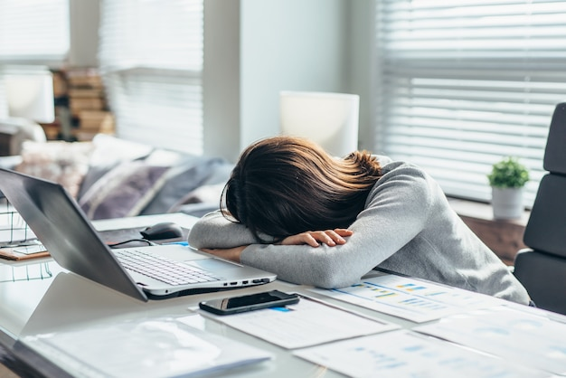 Woman in workplace is resting, tired of work.