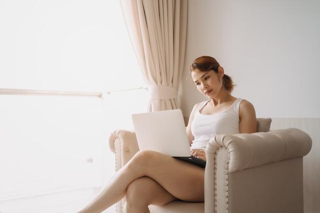 여자는 호텔에서 일하는 소파 개념에서 노트북으로 일하고 휴식을 취합니다.