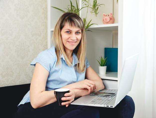 Женщина работает в домашнем офисе удаленно. фрилансер работает на компьютере
