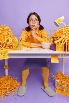 上に集中しているオフィスの机で働く女性は、紫に紙を切った後、新しいプロジェクトを作成することを考えていますキャビネットが混乱しています