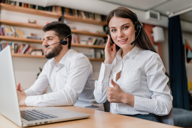 Woman works in call center with headset as dispatcher answering clients phone calls