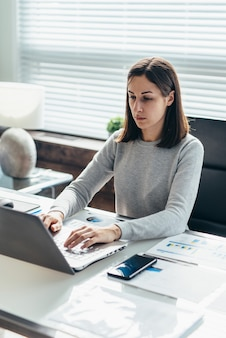Woman works at desk with laptop in office.