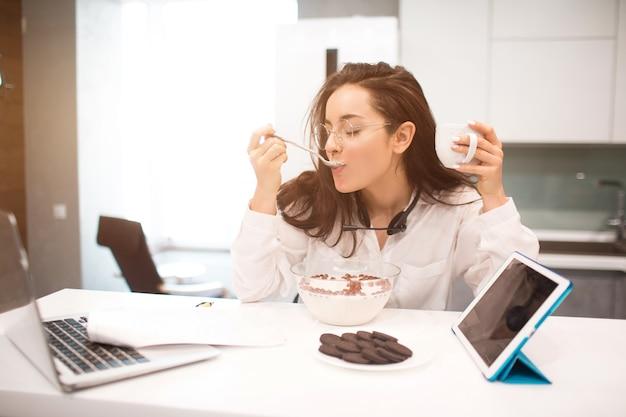 여자는 가정에서 작동합니다. 직원이 주방에 앉아 노트북과 태블릿으로 많은 작업을하고 화상 회의와 회의를합니다. 헤드셋과 함께 헤드폰을 사용합니다. 동시에 먹고 일합니다.