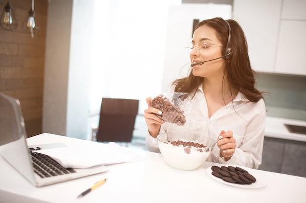 女性は自宅で仕事をしながら食事をします。