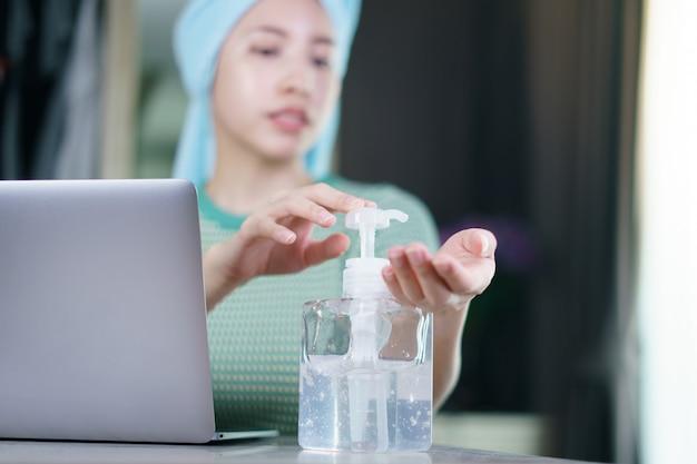 여자는 보호 마스크를 착용하고 소독제 젤로 손을 청소하는 검역소에서 집에서 일합니다.