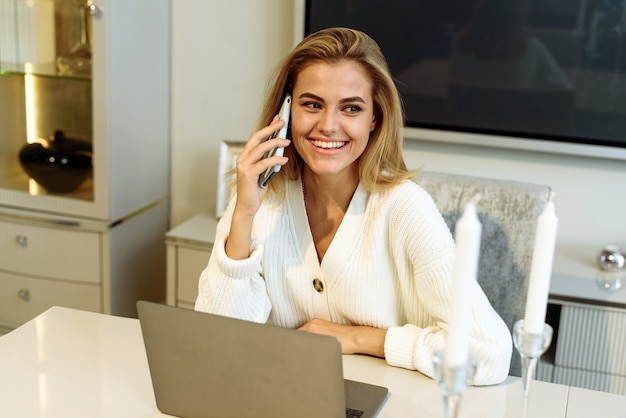 A woman works from home on a laptop and speaks on the phone with a business partner or boss.