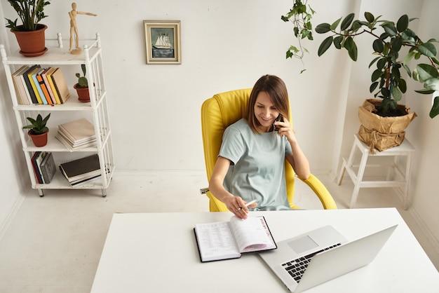 女性は居心地の良いホームオフィスで働いています