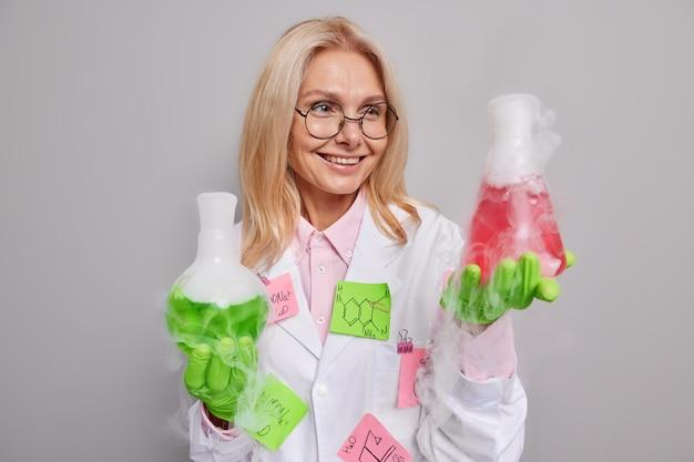 화학 실험실에서 일하는 여성은 약국 연구를 하게 하고 실험은 보호용 고무 장갑을 착용하고 성공적인 작업 후 증기로 물질을 봅니다.
