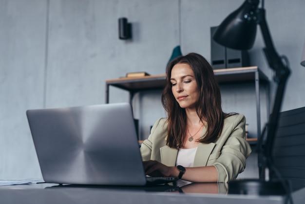 여자는 노트북으로 그녀의 책상에 앉아 그녀의 사무실에서 작동